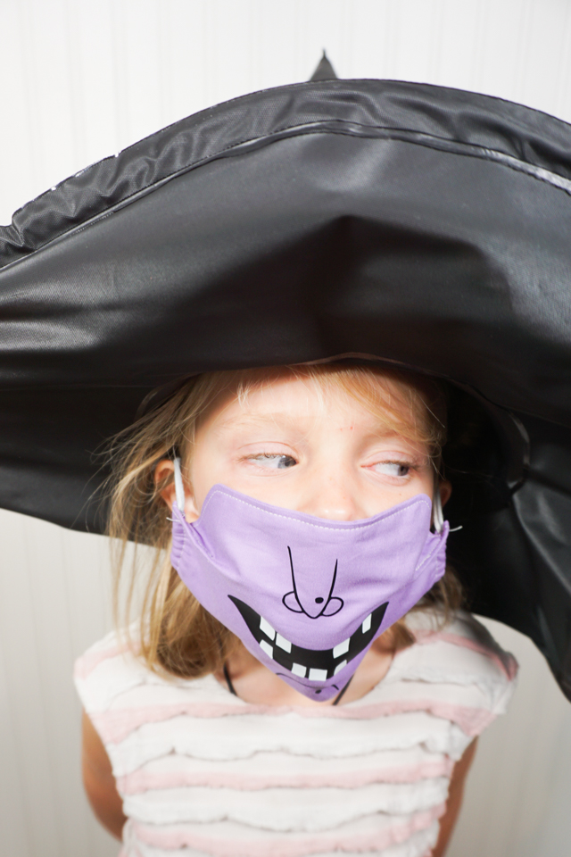 girl wearing witch mask