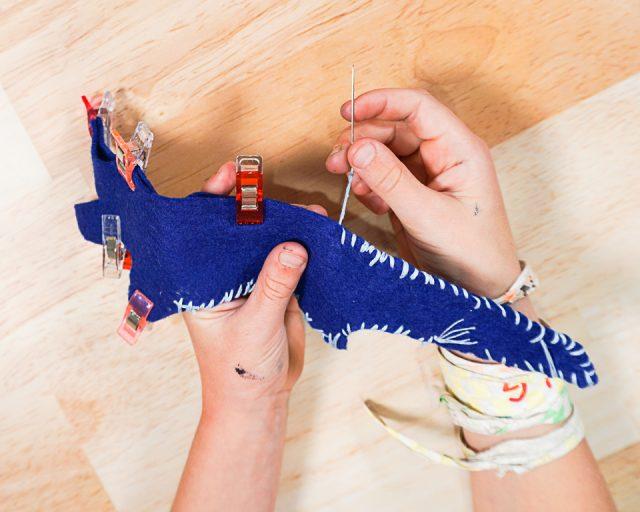 girl sewing felt alligator