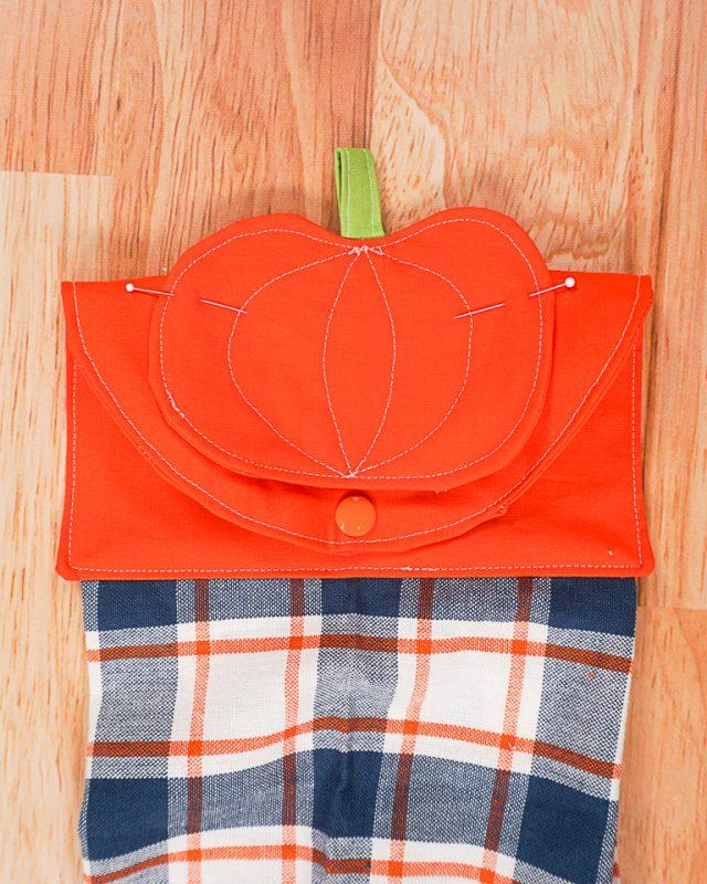 pin pumpkin onto fold of towel